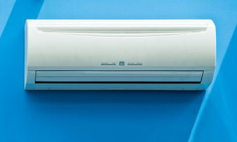 White air-conditioner on blue wall