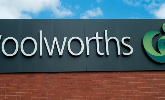 Woolworths sign on a brick wall, under a blue cloudy sky.