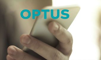 Person's hand using a mobile phone, with Optus logo over the top.