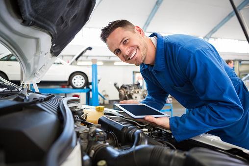 Mechanic smiling tablet car