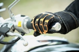 Yellow motorcycle glove holding bike handle
