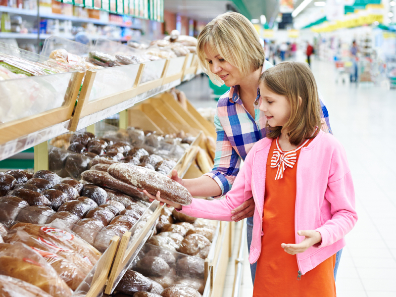 Mother and daughter choosing bread in supermarket
